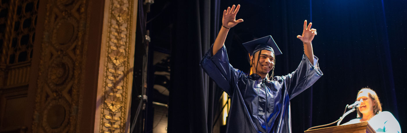 Graduating Senior celebrating with arms in the air